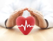 Heart pulse covered by hands. Health insurance concept stock image