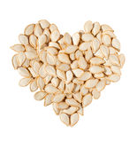 Heart from pumpkin seeds. Isolated on white background Royalty Free Stock Photos