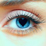 Heart in the pupil. Closeup shot of woman eye with heart in the pupil Stock Photos