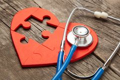 Heart puzzle red and stethoscope on wooden background. Concept diagnosis and treatment of heart disease, medical insurance.  stock image