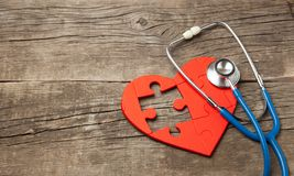 Heart puzzle red and stethoscope on wooden background. Concept diagnosis and treatment of heart disease, medical insurance. Copy space for text stock photo