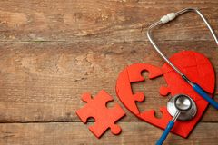 Heart puzzle red and stethoscope on wooden background. Concept diagnosis and treatment of heart disease, medical insurance. Copy space for text royalty free stock image