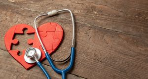 Heart puzzle red and stethoscope on wooden background. Concept diagnosis and treatment of heart disease, medical insurance. Copy space for text royalty free stock photo