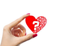 Heart questions. Woman hand is holding red heart shape with question marks inside of it isolated on white stock photo