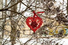 Heart in quilling techniques - symbol of Valentines Day. Lying on a thick branch of a tree in the winter before the holiday. Selective focus Royalty Free Stock Image