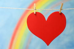 The heart symbol with a blue sky and colorful rainbow. Stock Photo