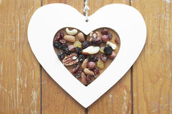 Heart, raisins and nuts on wooden background. Heart on wooden background, symbolic of love and health Royalty Free Stock Images