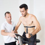 Heart rate monitor check on bike. Heart rate monitor with male trainer Royalty Free Stock Photo