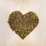 Heart of raw dry brown lentils in cup, top view. Heart shaped from raw dry brown lentils in cup, top view, square composition, food preparation, copy space Stock Photo