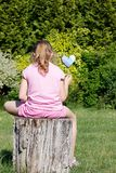 Heart. Rear view little girl sitting on stump and holding hand made heart in the garden Stock Photos