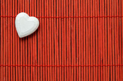 Heart on red bamboo top left corner Stock Photography