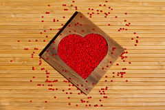 Heart from red beads in wooden heart-shaped box Stock Photography