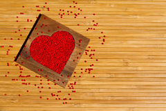 Heart from red beads in wooden heart-shaped box. On the background of bamboo Stock Photos