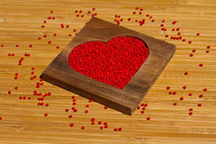 Heart from red beads in wooden heart-shaped box Royalty Free Stock Image