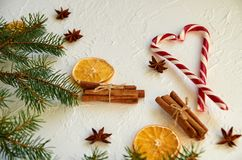 Heart of red candy cones on the white table with spices anise stars, cinnamon sticks, dried oranges and fir branches Stock Image
