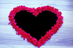 Heart of red confetti - black copy space and blue background Royalty Free Stock Photography