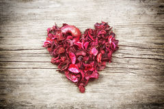 Heart from red dry petals on wooden table Royalty Free Stock Photos