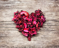 Heart from red dry petals on wooden table Royalty Free Stock Photo