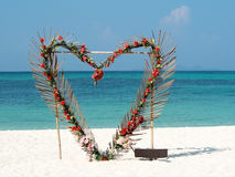 Heart from red flowers palm leafs on summer ocean beach background. Valentine, love, wedding concept. Clear sky, beautiful tropica Stock Image