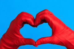 A heart of red leather. Two hands with red leather hands forming a heart Stock Photography