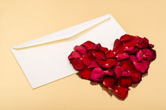 Heart of red petals lying on top of an open blank envelopes Stock Photo