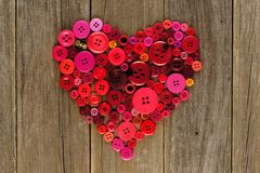 Heart of red and pink buttons on wood Royalty Free Stock Photos