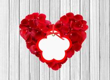 Heart from red rose petals and tag on wooden table Royalty Free Stock Image
