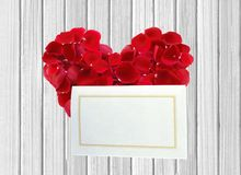 Heart from red rose petals and white card on wooden table Royalty Free Stock Photos