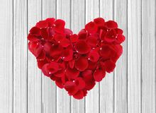 Heart from red rose petals on wooden table Stock Images