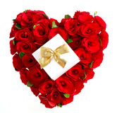Heart of red roses with gift and golden bow Stock Images