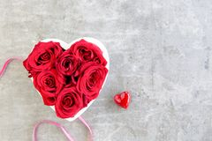 Heart of red roses on grey background with ribbon royalty free stock image