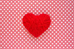 Heart of red threads on a background of cloth in polka dots. Red. Heart shape made from wool on textile red and white polka dots background. Yarn heart shape royalty free stock photos