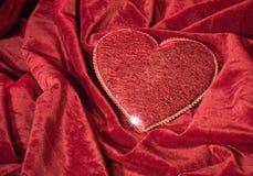 Heart on the red velvet Stock Photo