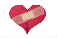 Heart repaired by bandaid. On white background Royalty Free Stock Photos