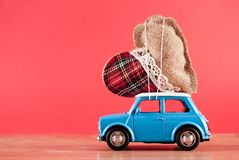 Heart on retro toy car on red background royalty free stock photo