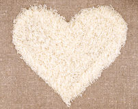Heart of rice grains on linen background. Fig heart . rice grains linen fabric . Heart of rice grains on linen background Royalty Free Stock Photo