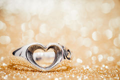 Heart ring on the floor with golden bokeh on background.  Royalty Free Stock Photos