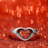 Heart ring on the floor with red bokeh on background.  stock photography