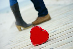 Heart on the road with man`s and woman`s feet. Red heart on the road with man`s and woman`s feet royalty free stock image