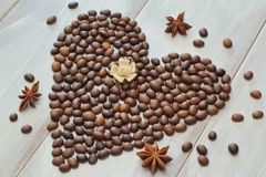 Heart of coffee beans with star of anise and satin in pastel shades of a rose on a light wooden background stock images