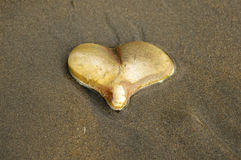 Heart Rock In Sand. Close up a rock in the shape of a heart laying in the sand Stock Photos