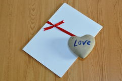 Heart rock on white paper tie red ribbon Royalty Free Stock Photo