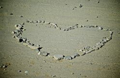 Heart of Rocks. Heart shape of different sized rocks on flat road surface Royalty Free Stock Images