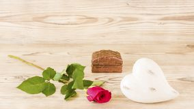 A heart and a rose with a gift. In front of a wood background Royalty Free Stock Images