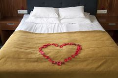 Heart from rose petals on a bed. Romantic concept stock photography