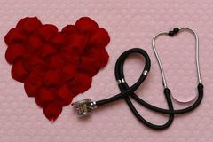Heart of rose petals and stethoscope stock image