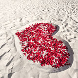 Heart of roses petals on sea sand beach Stock Photography