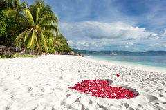 Heart of roses petals on sea sand beach Stock Photo
