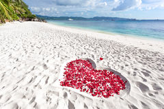 Heart of roses petals on sea sand beach Royalty Free Stock Images