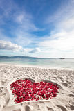 Heart of roses petals on sea sand beach Royalty Free Stock Image